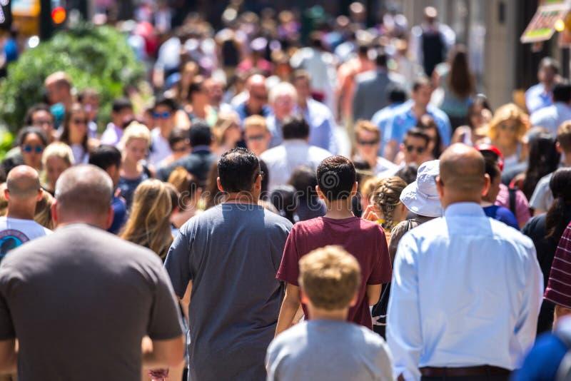 Muchedumbre de gente que camina en la acera de la calle imágenes de archivo libres de regalías