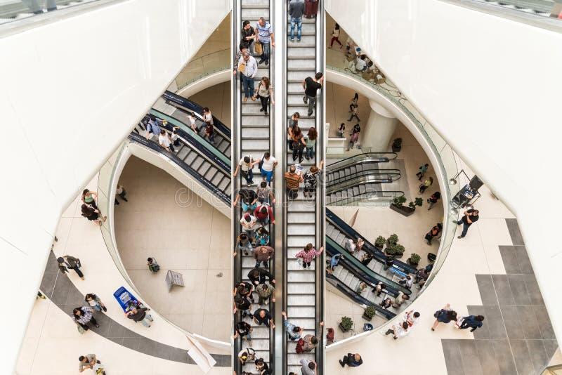 Muchedumbre de la gente en las escaleras móviles en alameda de compras de lujo imagenes de archivo