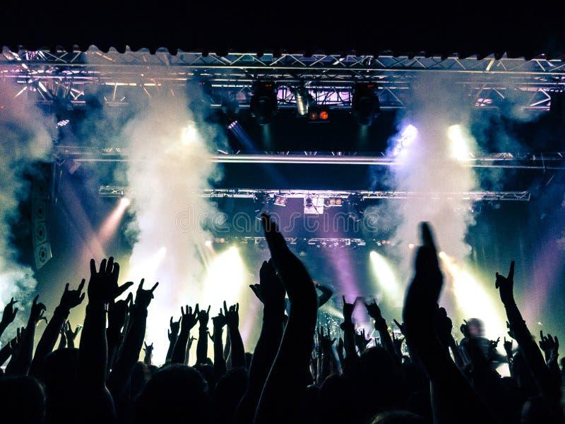Muchedumbre del concierto delante de luces de la etapa foto de archivo libre de regalías
