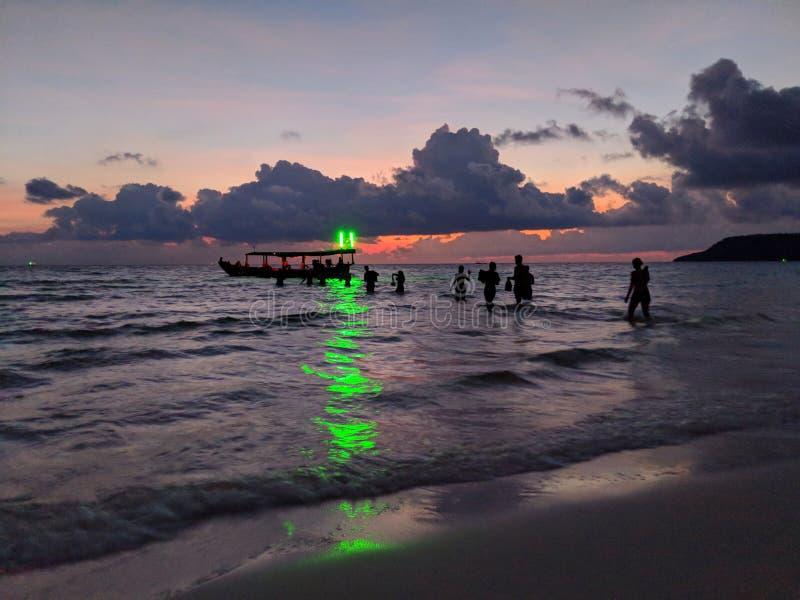 Muchedumbre del partido que vadea de nuevo al barco hacia luz verde de la playa en Koh Rong, Camboya foto de archivo