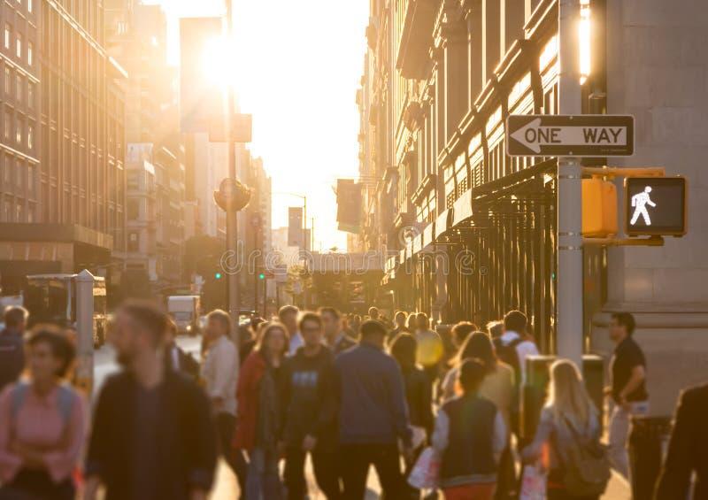 Muchedumbre diversa de gente anónima que camina abajo de una calle muy transitada en New York City foto de archivo