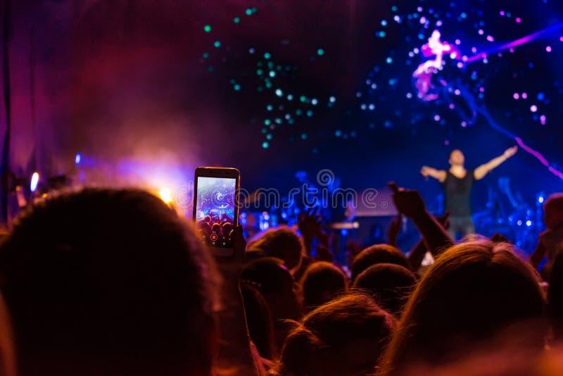 Muchedumbre en el concierto Siluetas de la gente en retroiluminado por las luces azules y púrpuras brillantes de la etapa Muchedu fotos de archivo libres de regalías