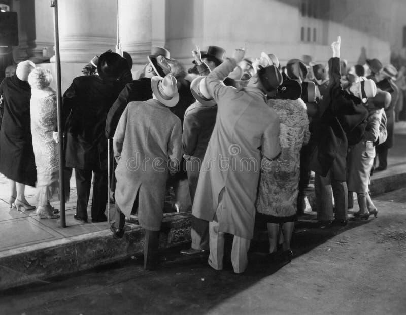 Muchedumbre en la calle que mira para arriba imagen de archivo