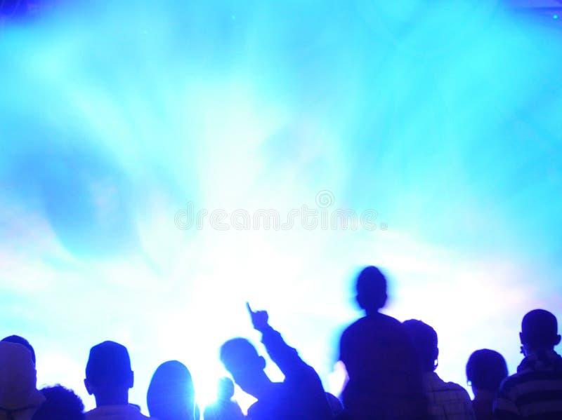 Muchedumbre enmascarada contra luz azul imagen de archivo