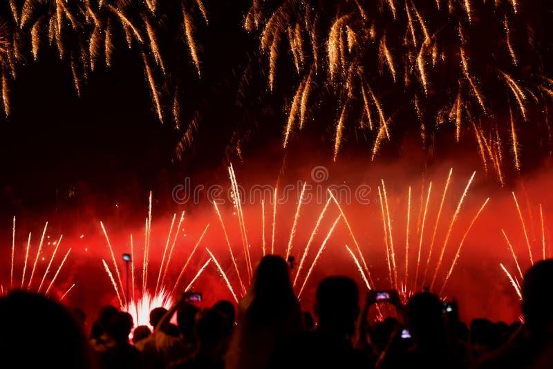 Muchedumbre irreconocible borrosa extracto de gente joven en el concierto, demostración de la diversión de los fuegos artificiale fotografía de archivo
