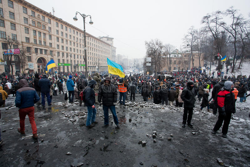 Muchedumbre loca de manifestantes que caminan en el cuadrado quemado después de lucha con policía en capital durante alboroto anti foto de archivo
