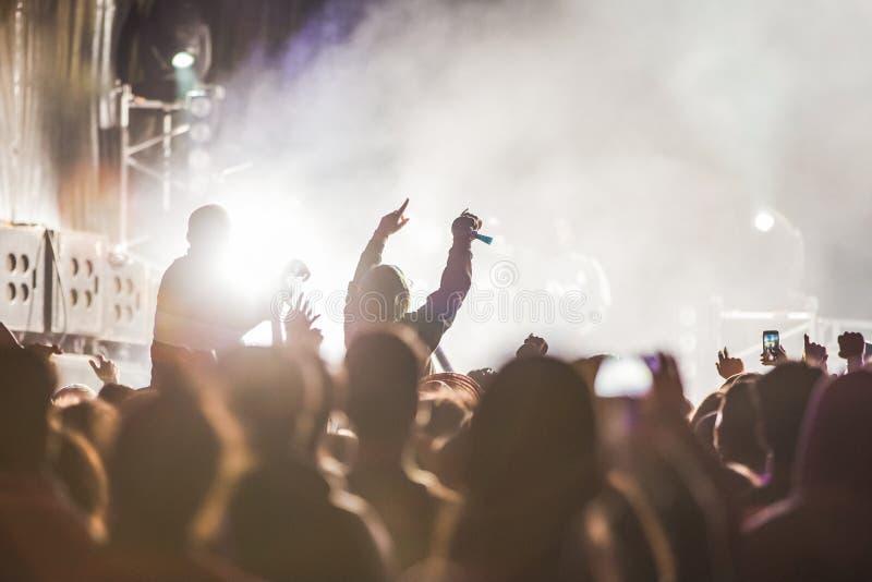 Muchedumbre que anima en el festival de música, adolescencias que se divierten imágenes de archivo libres de regalías