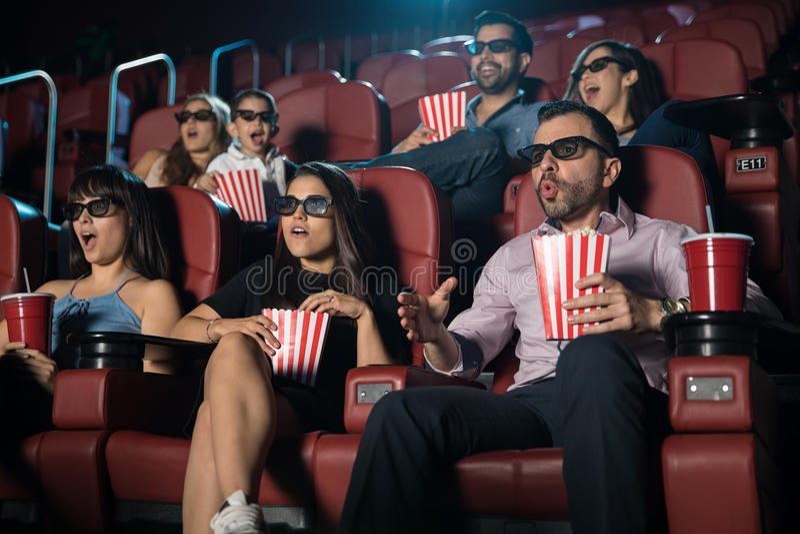 Muchedumbre sorprendida que mira la película 3d fotos de archivo