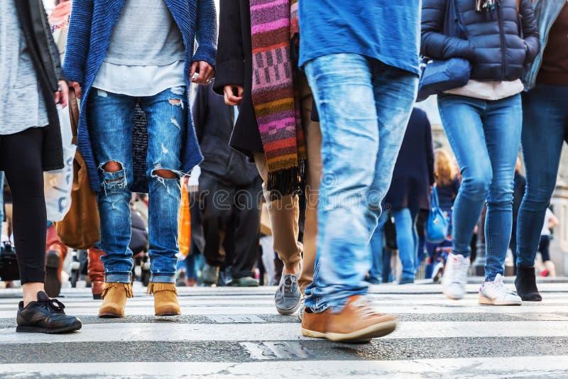 Muchedumbres de gente en la falta de definición de movimiento que cruza una calle de la ciudad imagen de archivo
