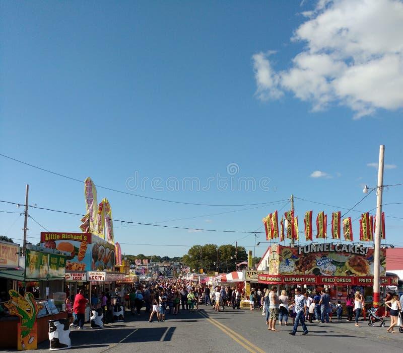 Muchedumbres de gente que camina la mitad del camino centraa en una feria del condado popular, Pennsylvania, los E.E.U.U. imagenes de archivo