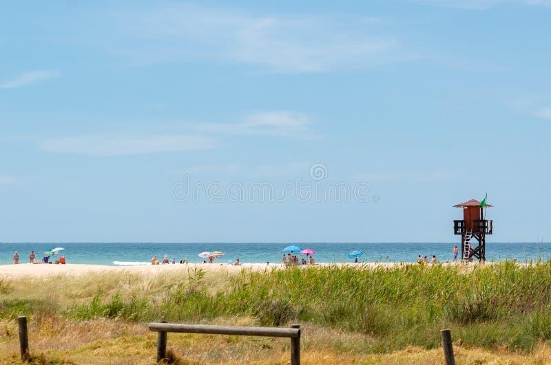Muchedumbres de turistas y de bañistas del sol que se divierten y que nadan cerca de una torre del rescate en Cádiz, España fotos de archivo