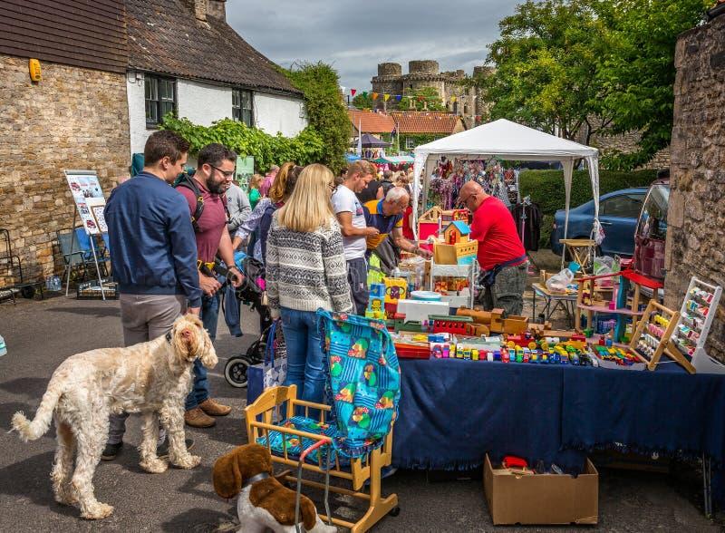 Muchedumbres que hacen compras en las paradas de calle durante Nunney Fayre en Nunney, Somerset, imagen de archivo