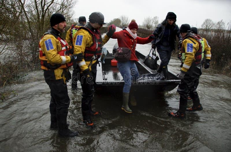 Muchelney Somerset Levels England UK 2014 Floods. UK Muchelney -- 31 Jan 2014 -- Police officers from Avon & Somerset Constabulary assist a woman to disembark royalty free stock photography