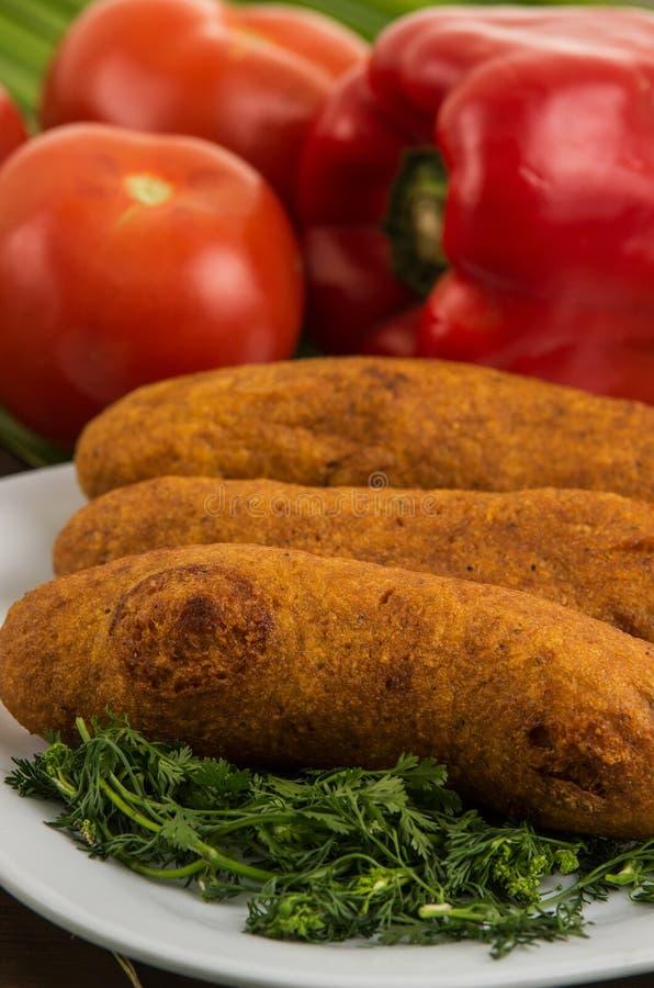 Muchin, een Ecuatoriaans typisch voedsel op een witte plaat met een vage tomaat en peper stock fotografie