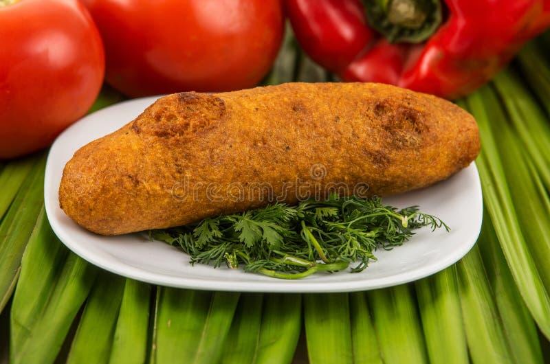 Muchin, een Ecuatoriaans typisch voedsel op een witte plaat met een vage tomaat en peper achter over een groen blad stock afbeeldingen