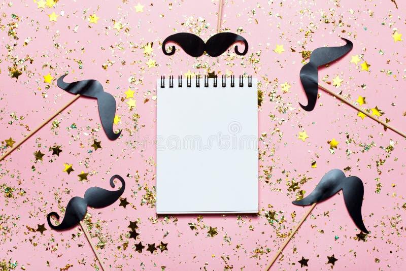 Mucho bigote de papel negro en fondo chispeante rosado con confeti y el cuaderno vacío con el lugar para el texto ilustración del vector