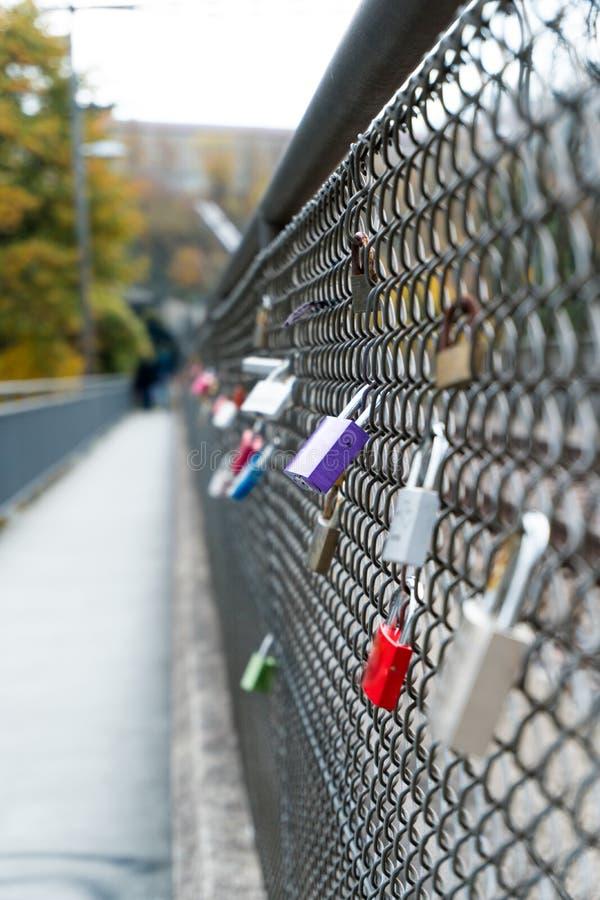 Mucho diversas cerraduras del color y del estilo y la verja del alambre de un puente que simboliza relaciones largas y amor román fotografía de archivo