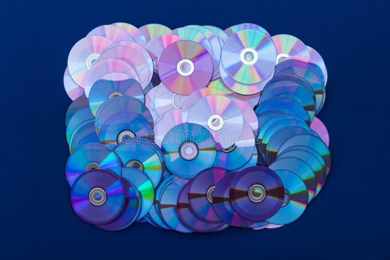 Mucho DVDs se apila en el paño azul fotografía de archivo libre de regalías