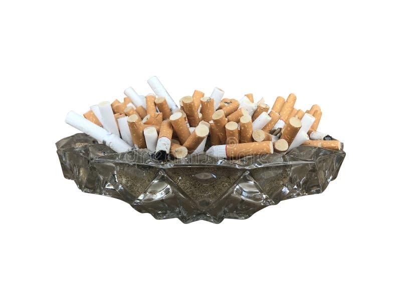 Mucho el cigarrillo que desborda un cenicero de cristal aislado en la trayectoria de recortes blanca del fondo incluye fotos de archivo