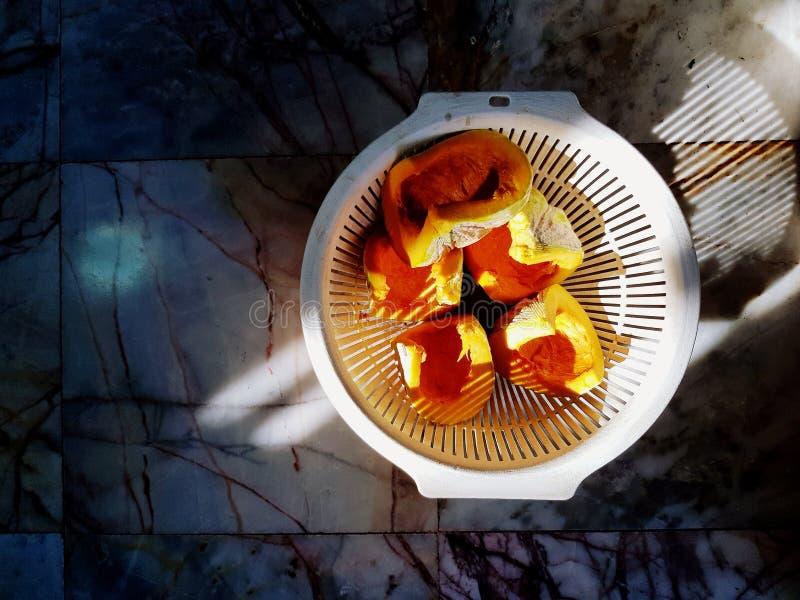 Mucho la calabaza de la frescura cortó poner en la cesta blanca en el piso de mármol con luz del sol por la mañana imagen de archivo
