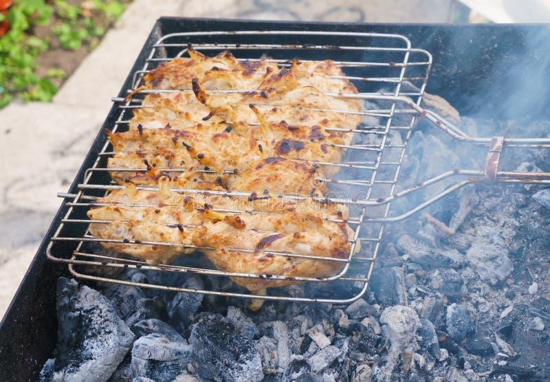 Mucho la carne de la carne asada del pollo junta las piezas con la cebolla en una parrilla foto de archivo libre de regalías