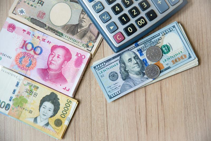 Mucho moneda del billete de banco, yen-Japón, euro-UE, yuan-China, ganar-Corea con la calculadora y las monedas Imagen para el fo imagenes de archivo