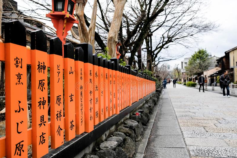 Mucho pequeño poste coloreado bermellón de la cerca con la escritura japonesa del kanji fotografía de archivo libre de regalías