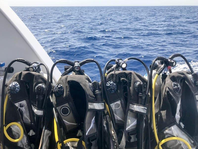 Mucho traje de salto negro con las mangueras y los buceadores que cuelgan en un soporte en un barco rápido, nave, línea de crucer imágenes de archivo libres de regalías