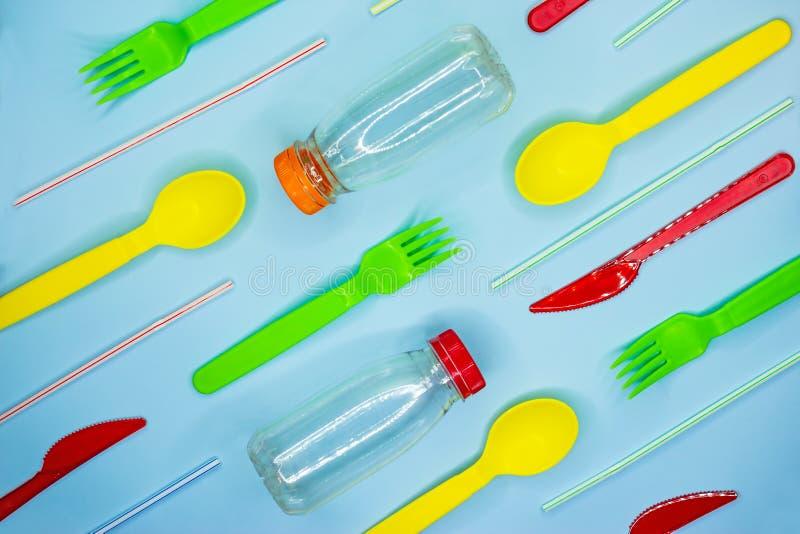 Mucho vajilla disponible colorido tal como bifurcaciones, cuchillos, cucharas, paja, botellas en un fondo azul claro el pl?stico  imágenes de archivo libres de regalías