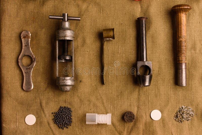 Muchos accesorios para los cartuchos de recarga de la caza mienten en el viejo fotografía de archivo