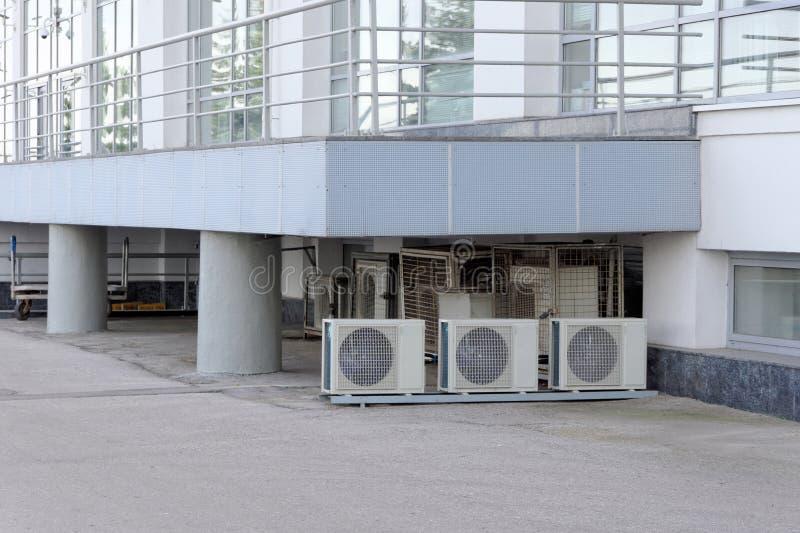 Muchos acondicionadores de aire instalados en el mismo lugar debajo del pórtico del edificio de oficinas foto de archivo