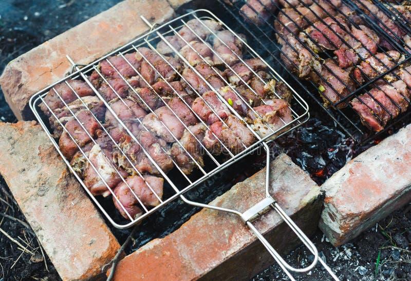 Muchos asan pedazos de la carne en una parrilla imagenes de archivo