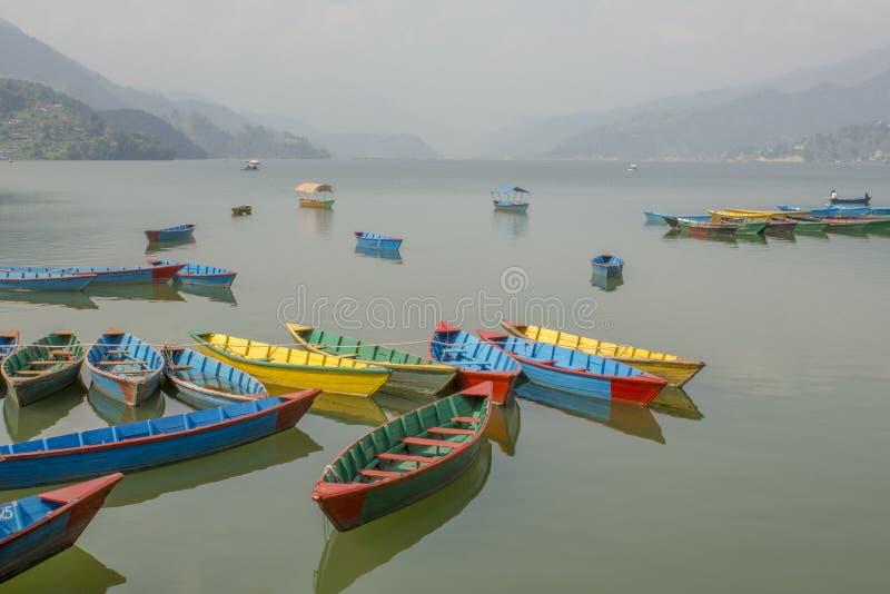 Muchos barcos coloreados de madera vacíos en un lago liso durante el día contra el contexto de un valle de la montaña imágenes de archivo libres de regalías