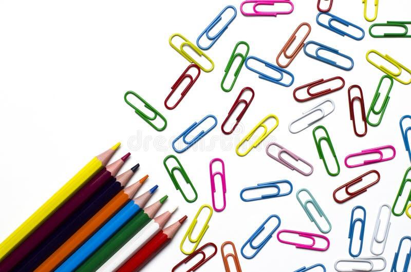 Muchos clips multicolores de los efectos de escritorio para los documentos y los lápices multicolores mienten en un fondo blanco fotos de archivo