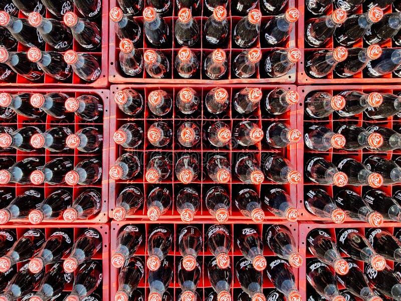 Muchos coquizan o la botella de la Coca-Cola en los cajones plásticos para entregado a los clientes imágenes de archivo libres de regalías