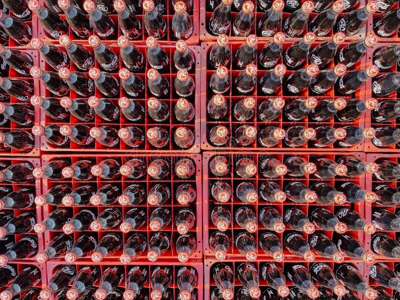 Muchos coquizan o la botella de la Coca-Cola en los cajones plásticos para entregado a los clientes fotos de archivo