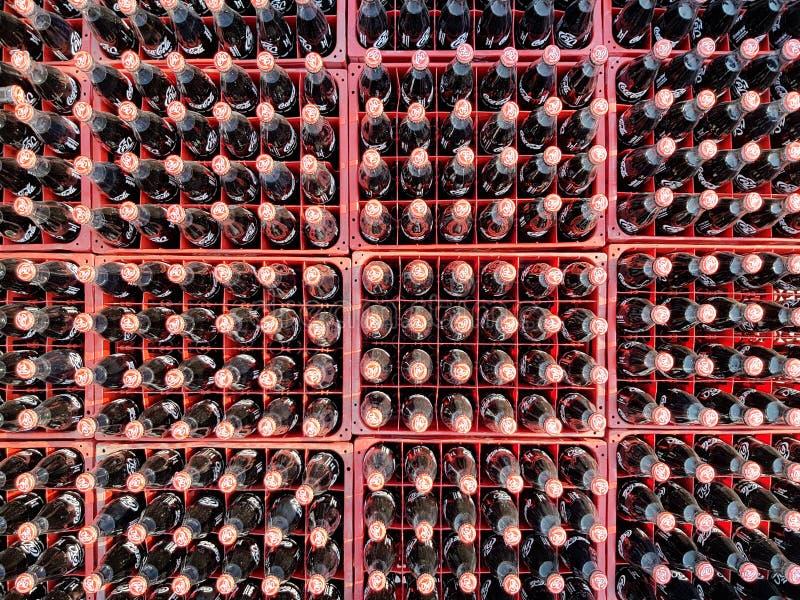 Muchos coquizan o la botella de la Coca-Cola en los cajones plásticos para entregado a los clientes imagen de archivo