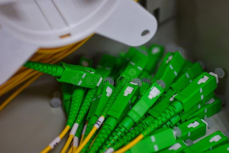Muchos cordones de remiendo ópticos en el gabinete de las telecomunicaciones fotos de archivo