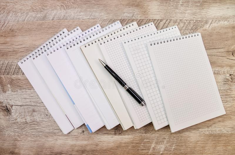 Muchos cuadernos blancos y una pluma en un fondo de madera imagen de archivo