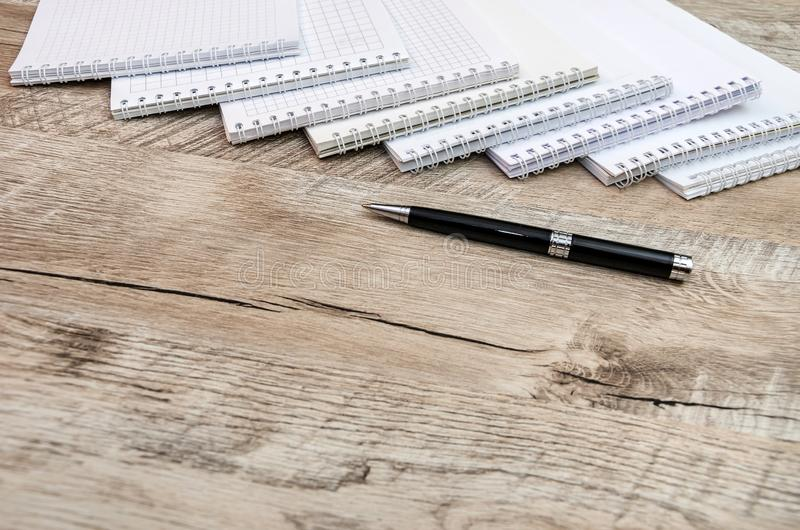 Muchos cuadernos blancos y una pluma en un fondo de madera imagen de archivo libre de regalías