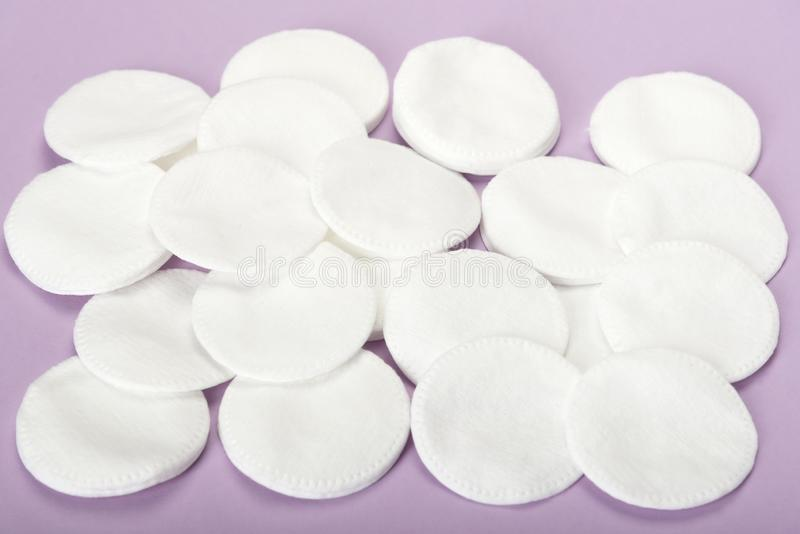 Muchos discos cosméticos del algodón en un fondo rosado imagen de archivo libre de regalías