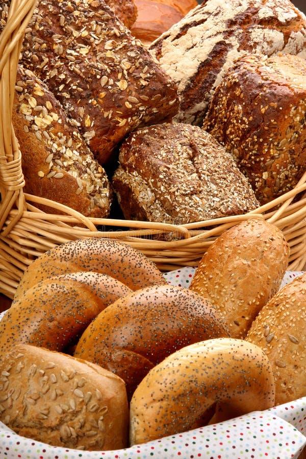 Muchos diversos tipos de pan y de rollos en cesta de mimbre imagenes de archivo