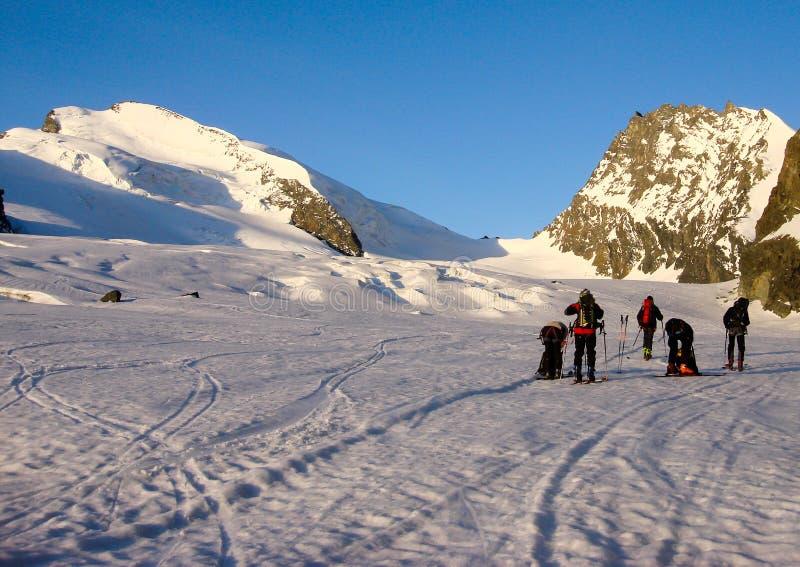 Muchos esquiadores backcountry consiguen listos para subir un alto pico alpino en las montañas cerca de Zermatt enseguida después imágenes de archivo libres de regalías