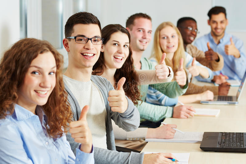 Muchos estudiantes que detienen los pulgares fotografía de archivo