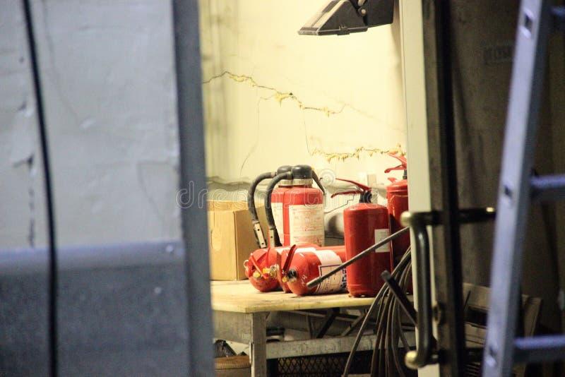 Muchos extintores en la tabla en la despensa vieja, enmarcando blur imágenes de archivo libres de regalías