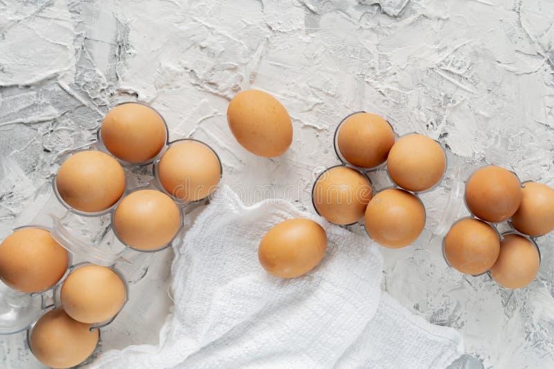 muchos huevos crudos crudos en una bandeja pl?stica en la tabla del grunge, dietas especiales del pollo del huevo fotografía de archivo