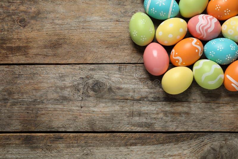 Muchos huevos de Pascua pintados coloridos en el fondo de madera, visión superior fotos de archivo libres de regalías