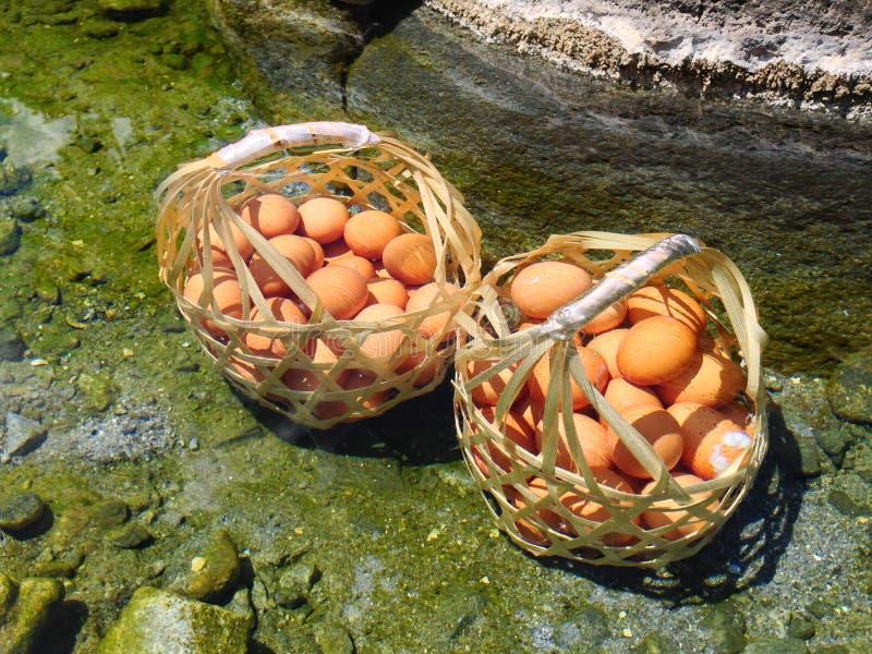 Muchos huevos del pollo en la cesta de madera hervida en las aguas termales foto de archivo