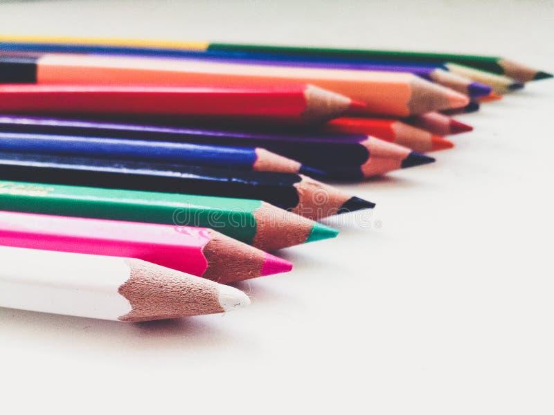 Muchos lápices afilados multicolores ponen en una superficie blanca en un estado dispersado fotografía de archivo