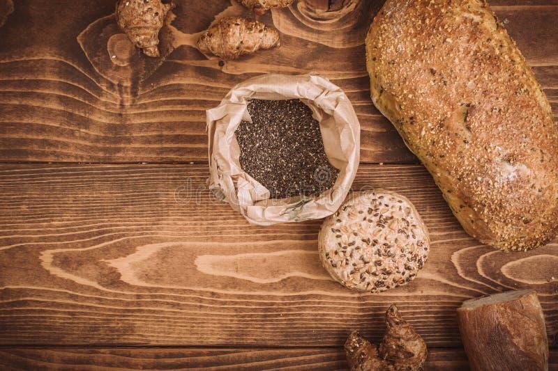 Muchos mezclaron los panes y los rollos cocidos en la tabla de madera rústica fotografía de archivo